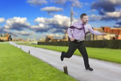 Running businessman in a hurry with modern city in Stock Photography