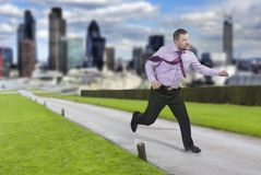 Running businessman in a hurry with modern city in Royalty Free Stock Images