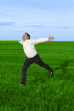 Running businessman in the meadow. Over clouds background Stock Photo