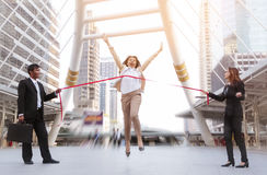 Running businesswoman crossing finish line Royalty Free Stock Images
