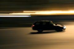 Running car - panning. Motion blur (panning) or a running black car at night Royalty Free Stock Photos