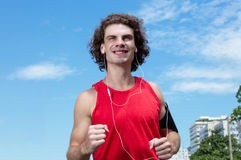 Running caucasian guy with long hair. Outdoor in the city Royalty Free Stock Photos