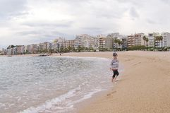 Running child on the beach. Amazing view on beach and sea. Blanes, Costa Brava, Catalonia, Spain royalty free stock photo
