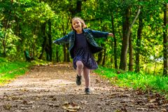 Running child. Happy child running through the park Royalty Free Stock Image