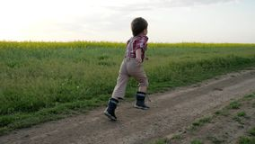 Running child, little boy runs along field road, happy kid having fun outside city, healthy childhood, clean environment stock video