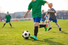Running Children Football Players. Kids Playing Soccer Match. Football Players Duel on Grass Pitch royalty free stock image