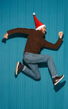 The running christmas man wearing a santa hat Stock Photos