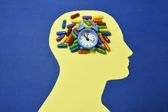 Running clock and colored pills on male head contour. Colored pills and small bell ring alarm clock , running and placed on an yellow male head contour , against Stock Images