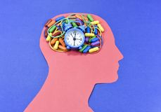 Running clock, colored pills and rubber bands on head contour Royalty Free Stock Image