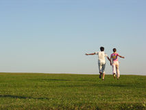 Running couple. Green grass stock photos
