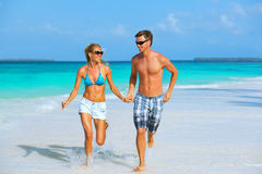 Running couple on the beach. Cheerful sportive young couple running on the beach with tan and sunglasses Royalty Free Stock Images