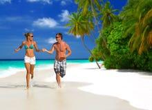 Running couple on the beach Stock Photo