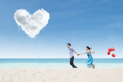 Running couple at beach under heart cloud Royalty Free Stock Photos