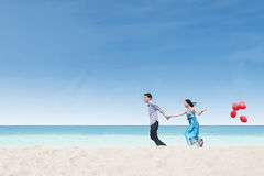 Running couple at beach wih balloons Stock Image