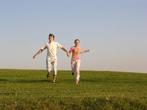 Running couple on grass Royalty Free Stock Photos