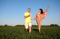 Running couple green meadow. A man and a woman running on grassland stock image