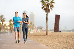 Running couple jogging Barcelona Beach Barceloneta. Running couple jogging on Barcelona Beach, Barceloneta. Healthy lifestyle people runners training outside on Royalty Free Stock Photos