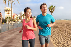 Running couple jogging Barcelona Beach Barceloneta. Running couple jogging on Barcelona Beach, Barceloneta. Healthy lifestyle people runners training outside on Stock Image