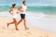 Running couple jogging on beach exercising sport Stock Photography