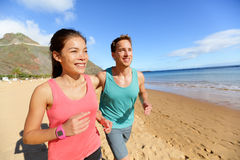 Running couple jogging on beach exercising. And jogging training. Runners working out on summer beach Stock Photo