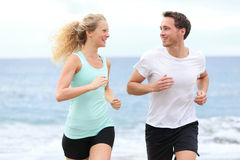Running couple jogging exercising on beach talking. And training as part of healthy lifestyle. Two fit runners jogging happy and smiling during workout stock photo