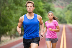 Running couple jogging on road. Runners training for marathon run sprinting. Active young multiracial couple in active healthy lifestyle concept. Asian women royalty free stock photography