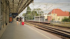 Running couple with a suitcase in a train station stock footage