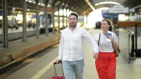 Running Couple With A Suitcase In A Train Station. Woman Holding Passports In Her Hands. stock footage