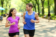 Running couple training in Central Park, New York. City (NYC). Happy runners talking together during run on famous Mall walk path under trees in Manhattan Royalty Free Stock Photography