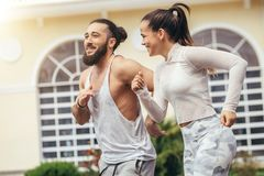 Running couple training outdoors working out against fitness centre. City positive runners jogging outdoor. Fit caucasian couple working out against fitness Royalty Free Stock Photos