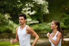 Running Couple. Young couple running in the summer park Royalty Free Stock Image