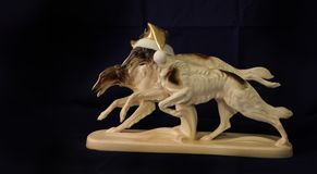 Running dogs statuette. Running dogs porcelain figurine on a dark background dedicated to the new year dog stock images