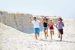 Running down beach. Happy friends running down sandy beach on hot day Stock Photography