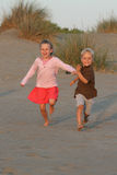 Running down the hill. Boy and girl runing in the sand royalty free stock image