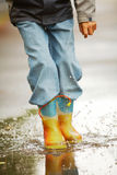 Running down puddles. Legs of happy lad running down puddle and making splashes Royalty Free Stock Photography