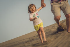 Running down the sand dunes. Little girl running down the sand dunes with her father in the Natural Reserve of Dunes of Maspaloma in Gran Canaria Royalty Free Stock Photo