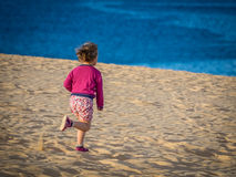 Running down the sand dunes. Little girl running down the sand dunes in  the Parque Natural of Dunes in Corralejo, Fuerteventura, Canary Islands, Spain Stock Photo