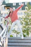 Running down the stairs. Happy energetic kid jumping on steps in casual wear. Energetic little girl with long hair. Braids in motion. Energetic small child stock image