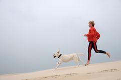 Running on the dune. Woman with dog running on the dune Royalty Free Stock Photo