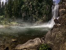 Running Eagle Falls. A rushing mountain waterfall with an American Bald Eagle perched on a rocky cliff – June 2006 Royalty Free Stock Photography
