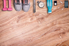 Running equipment. Dumbbells and running shoes, analog stopwatch and smartphone. stock photography
