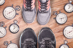 Running equipment. Stopwatch and running shoes. Time for run. Sport running accessories on the wooden floor. Sports rivalry. Royalty Free Stock Photography