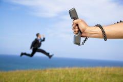 running för affärsmanholdingtelefon arkivbild