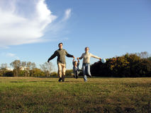 Running family autumn. Meadow stock images