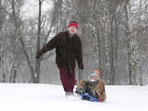 Running family on sled. winter Stock Photos