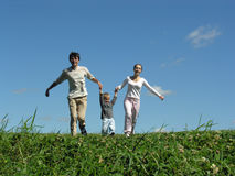 Running family sunny day 2. Blue sky green grass royalty free stock photos