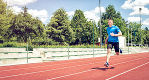 Running fast on athletic field track. Running fast on athletic track. Young adult man sprinting fast during hot summer day. Toned image royalty free stock photos