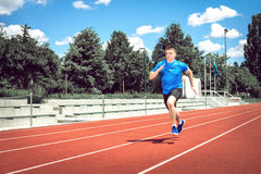Running fast on athletic field track. Running fast on athletic track. Young adult man sprinting fast during hot summer day. Toned image Royalty Free Stock Image
