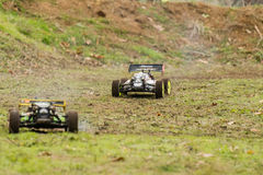Running fast. Two remote controlled cars on dirty race track Royalty Free Stock Image
