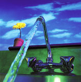 Running faucet. Water flowing from a faucet with a flower pot on the windowsill Stock Photography